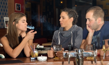 group of three people in bar smoking and drinking