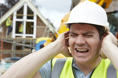 man with hard hat on building site holding his ears